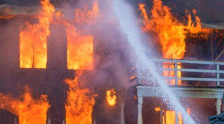 foto van brandend huis die wordt geblust bij artikel over uitkering naar herbouwwaarde, sloopwaarde of verkoopwaarde