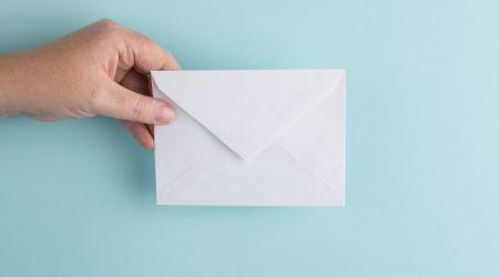 foto van een hand met envelop bij artikel over aansprakelijkstelling