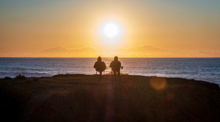 gepensioneerden die naar een zonsondergang boven zee kijken