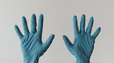 twee handen met blauwe chirurgen handschoenen