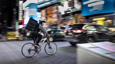 bezorger op fiets in het verkeer bij artikel over aansprakelijkheid en schadevergoeding bij ongeval maaltijdbezorger