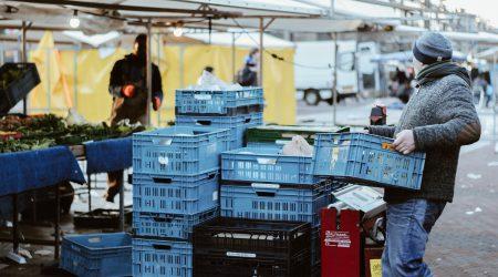foto man die krat tilt op de markt bij artikel over aansprakelijkheid voor schade veroorzaakt door werknemers