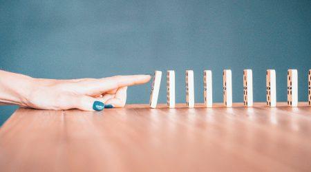 foto van vinger die dominosteen om duwt bij artikel over causaliteit in het verzekeringsrecht